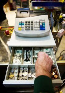 Picture of an employee with their hand in the till